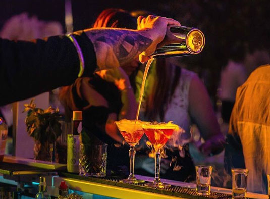 mobile cocktail bartending staff pouring a martini