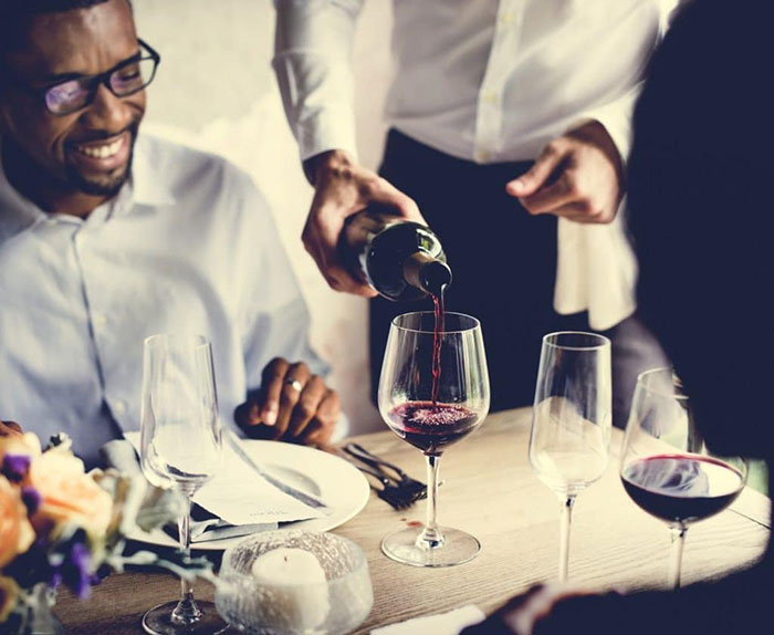 waitstaff for hire pouring a glass of wine at a party